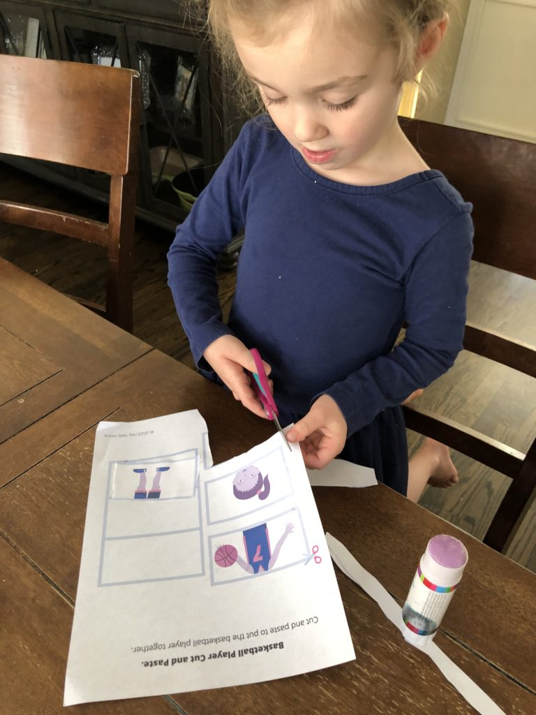 Daughter holding scissors correctly and working on free preschool cutting workbook page